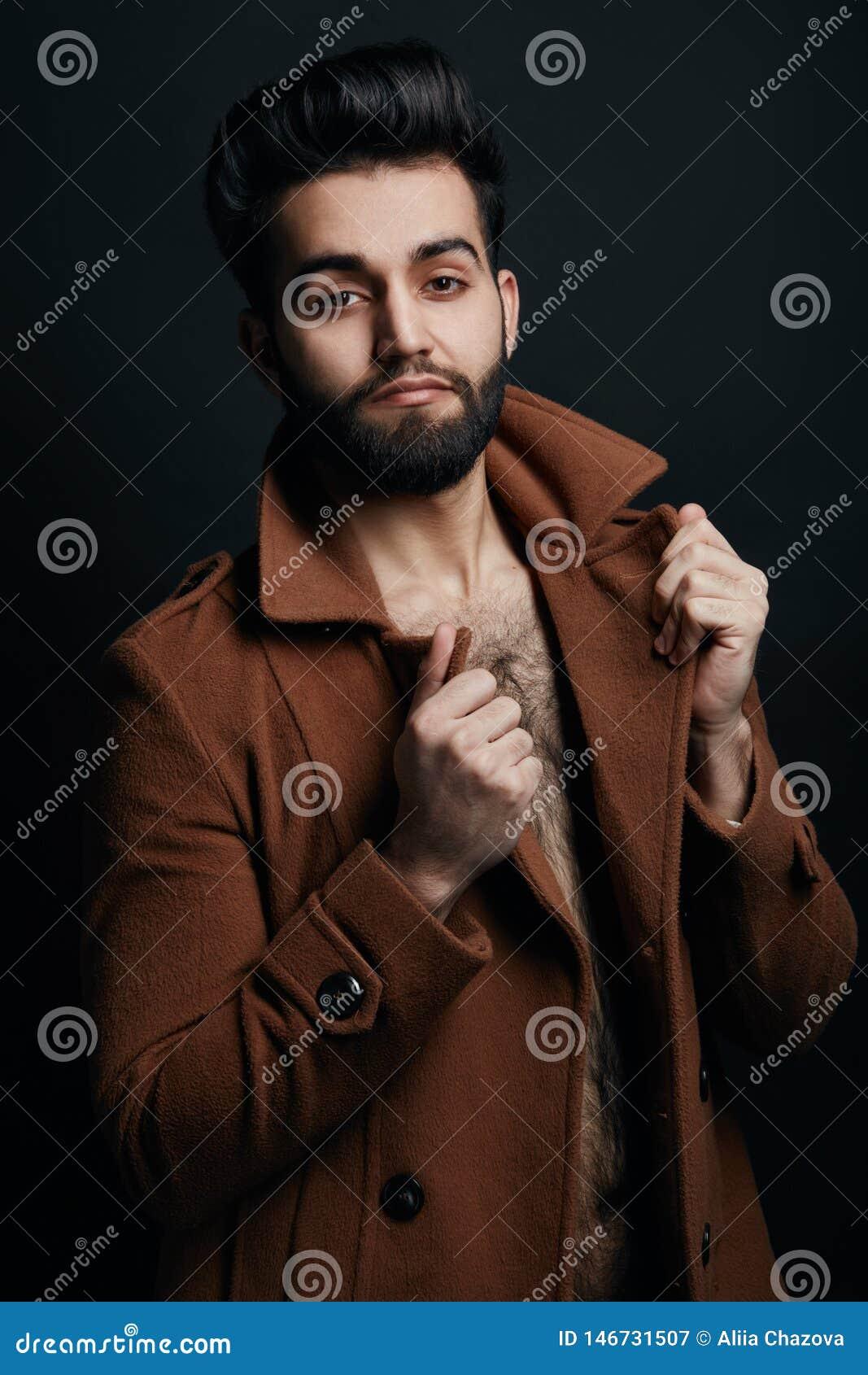 Machista elegante que toca el cuello de su capa y que presenta a la cámara