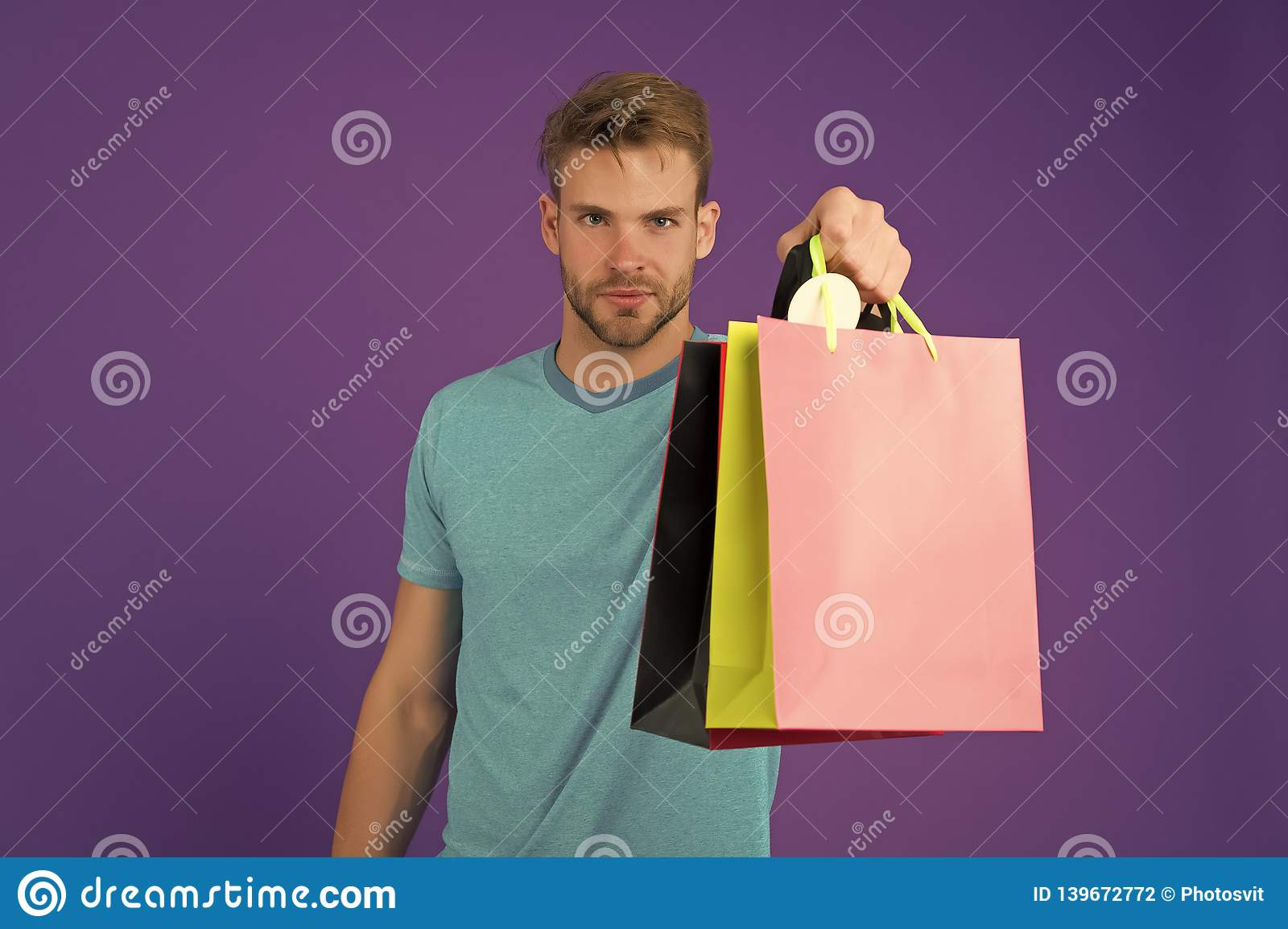 Macho with colorful paper bags on violet background. Man with shopping bags. Fashion shopper in casual blue tshirt