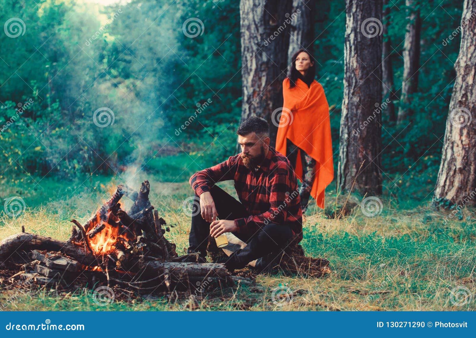 Macho com a cerveja que senta-se perto da fogueira, férias com esposa