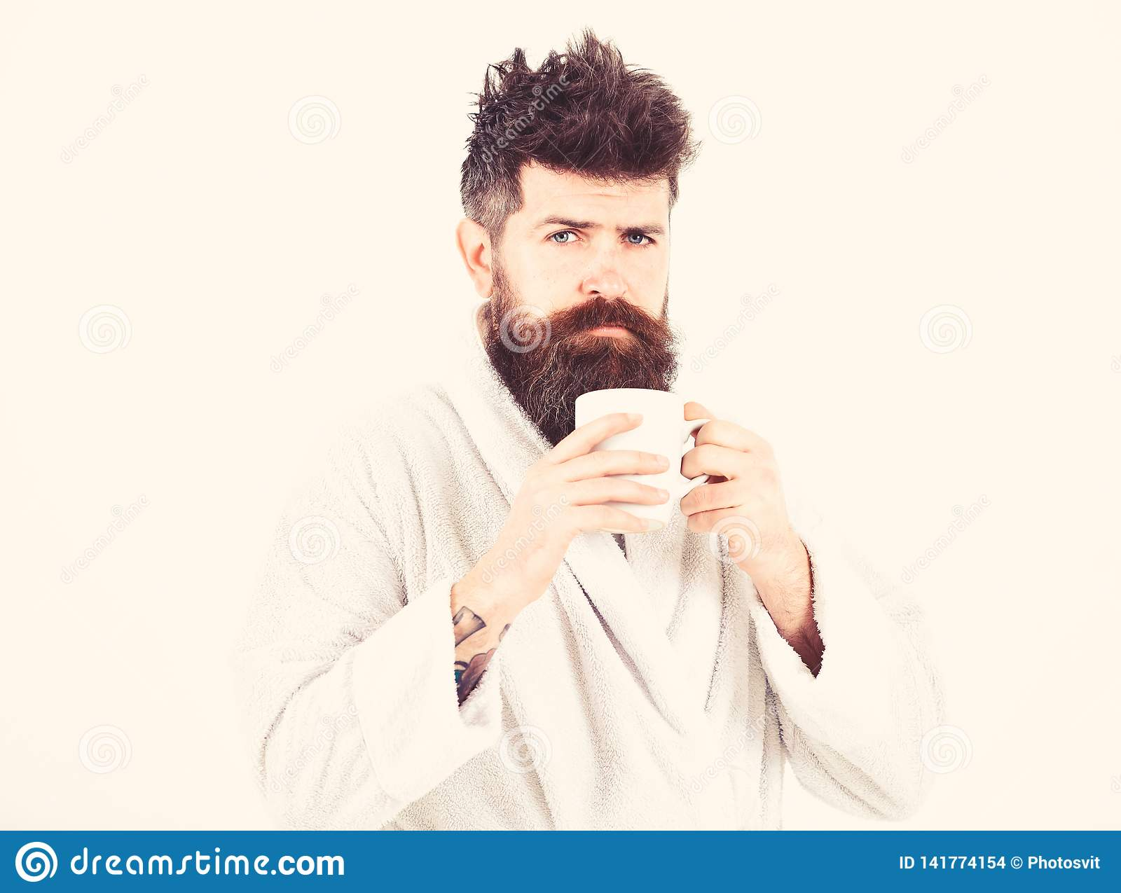 Macho drowsy, sleepy with strict face drinks coffee in morning. Morning rituals concept. Man with beard and disheveled