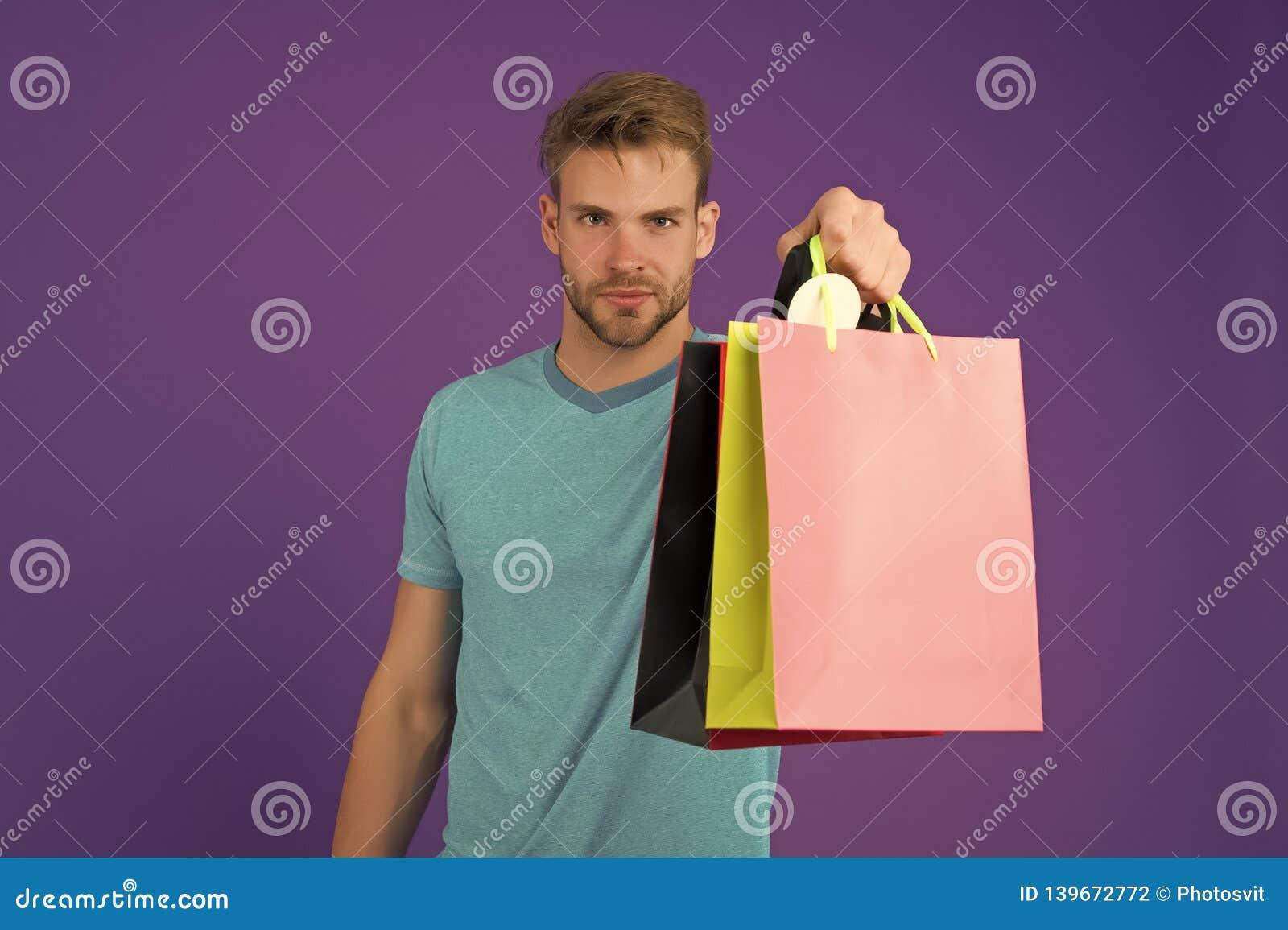 Macho med färgrika pappers- påsar på violett bakgrund shopping för påseman Modeshoppare i tillfällig blå tshirt