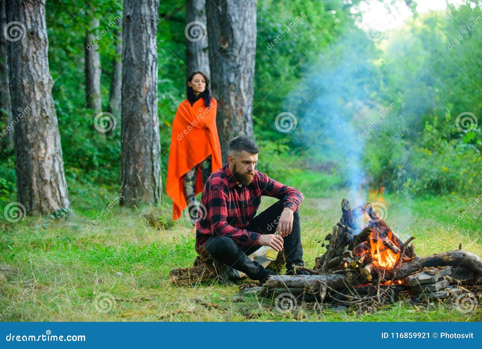 Macho met bierzitting dichtbij vuur, vakantie met vrouw