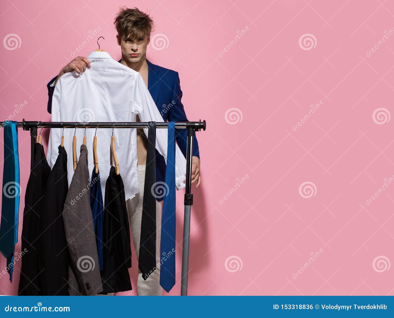 Macho wybiera koszula w garderobie na r??owym tle