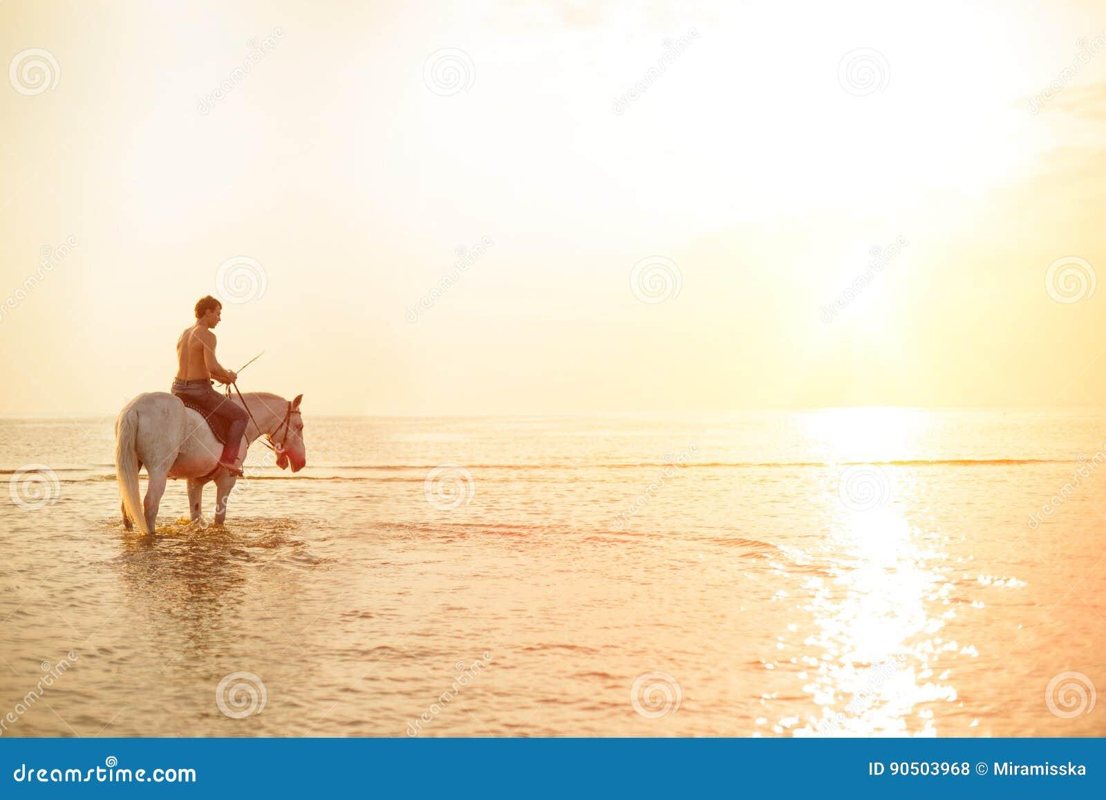 Machomann und Pferd auf dem Hintergrund des Himmels und des Wassers Jungenmodus
