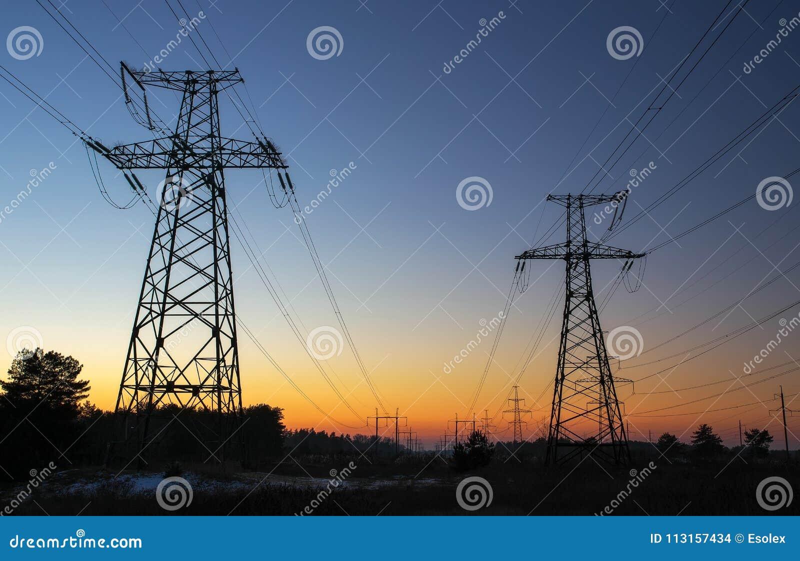 Machtslijnen met hoog voltage tijdens zonsopgang