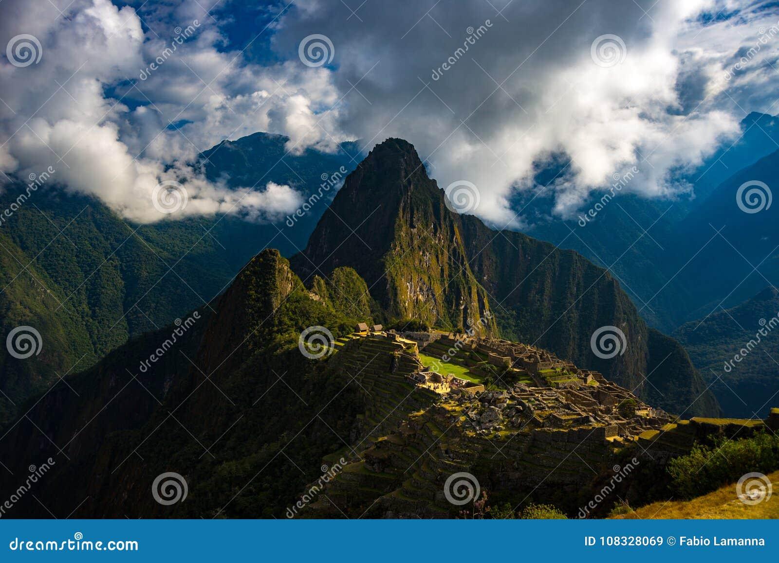 Machu Picchu door zonlicht wordt verlicht die uit uit de het openen wolken komen die De stad van Inca ` s is meest bezochte reisb