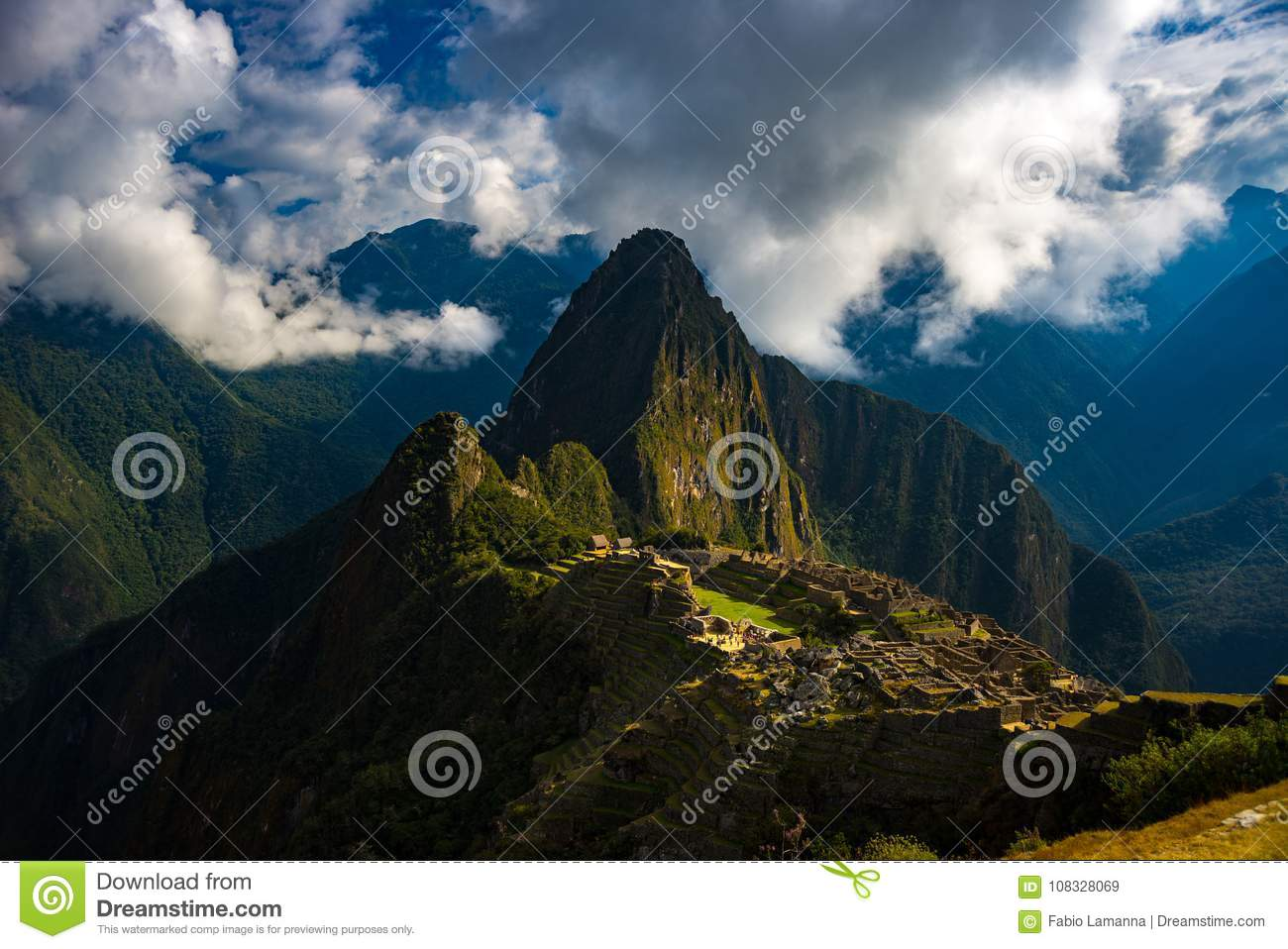 Machu Picchu illuminated by sunlight coming out from the opening clouds. The Inca`s city is the most visited travel destination i