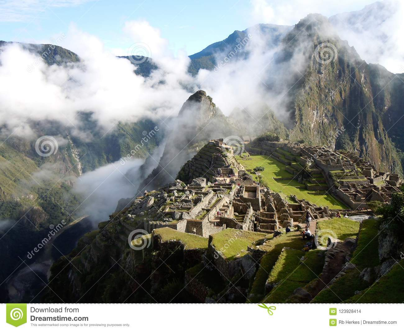 Machu Picchu on mountain top surrounded by clouds above, around and below in deep valley