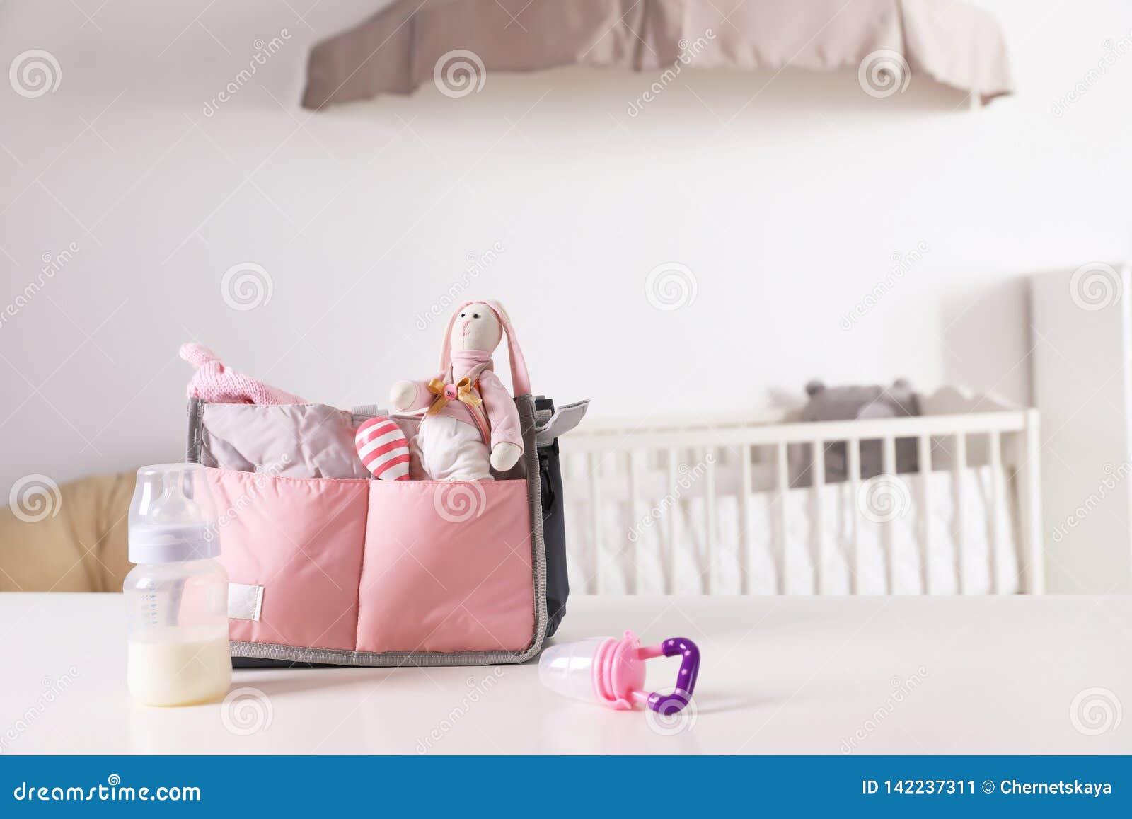 Macierzyńska torba z dzieci akcesoriami na stole