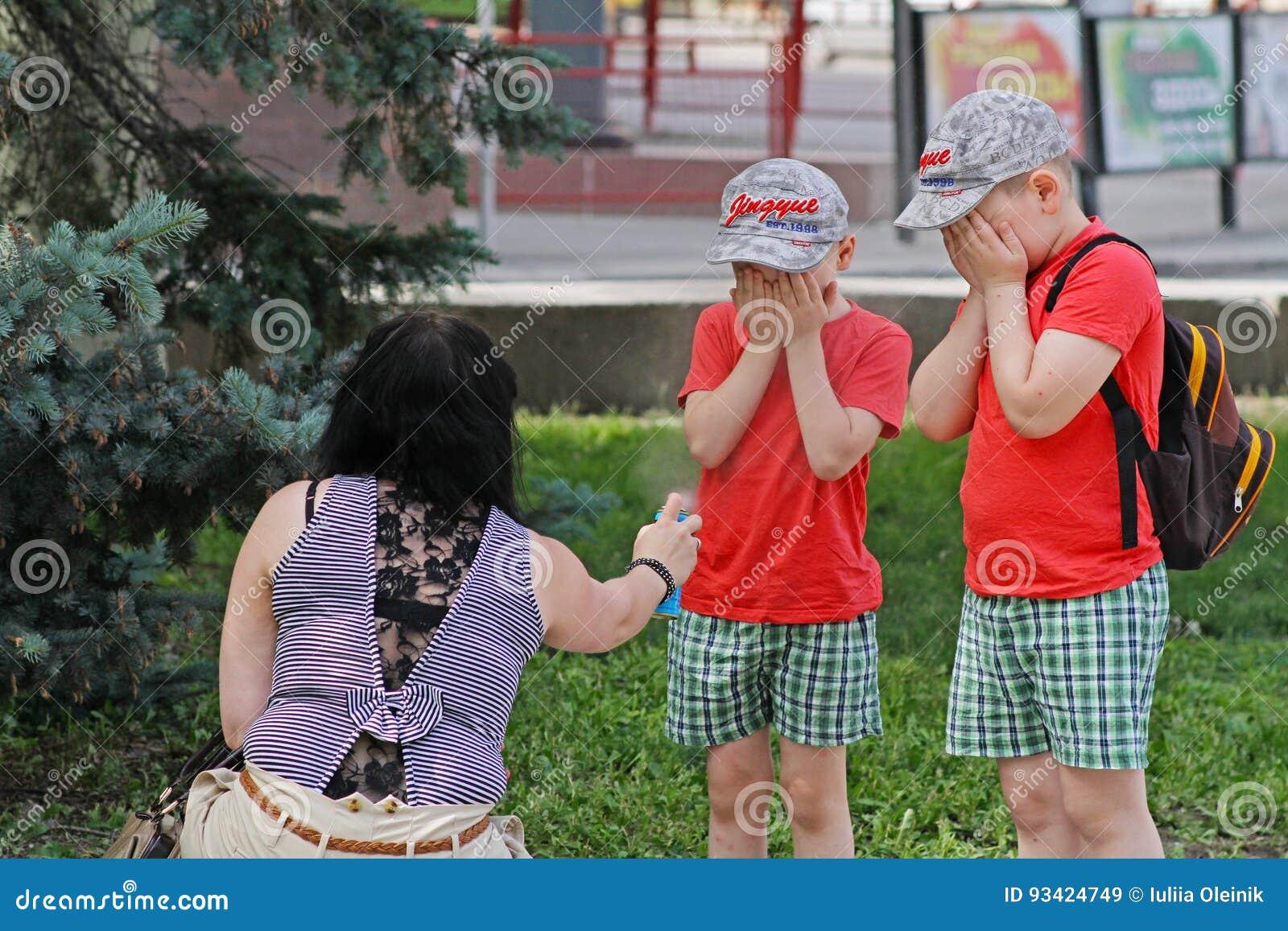 Macierzyści opryskiwanie insekta repellents na dzieciach z kiści butelką w Volgograd