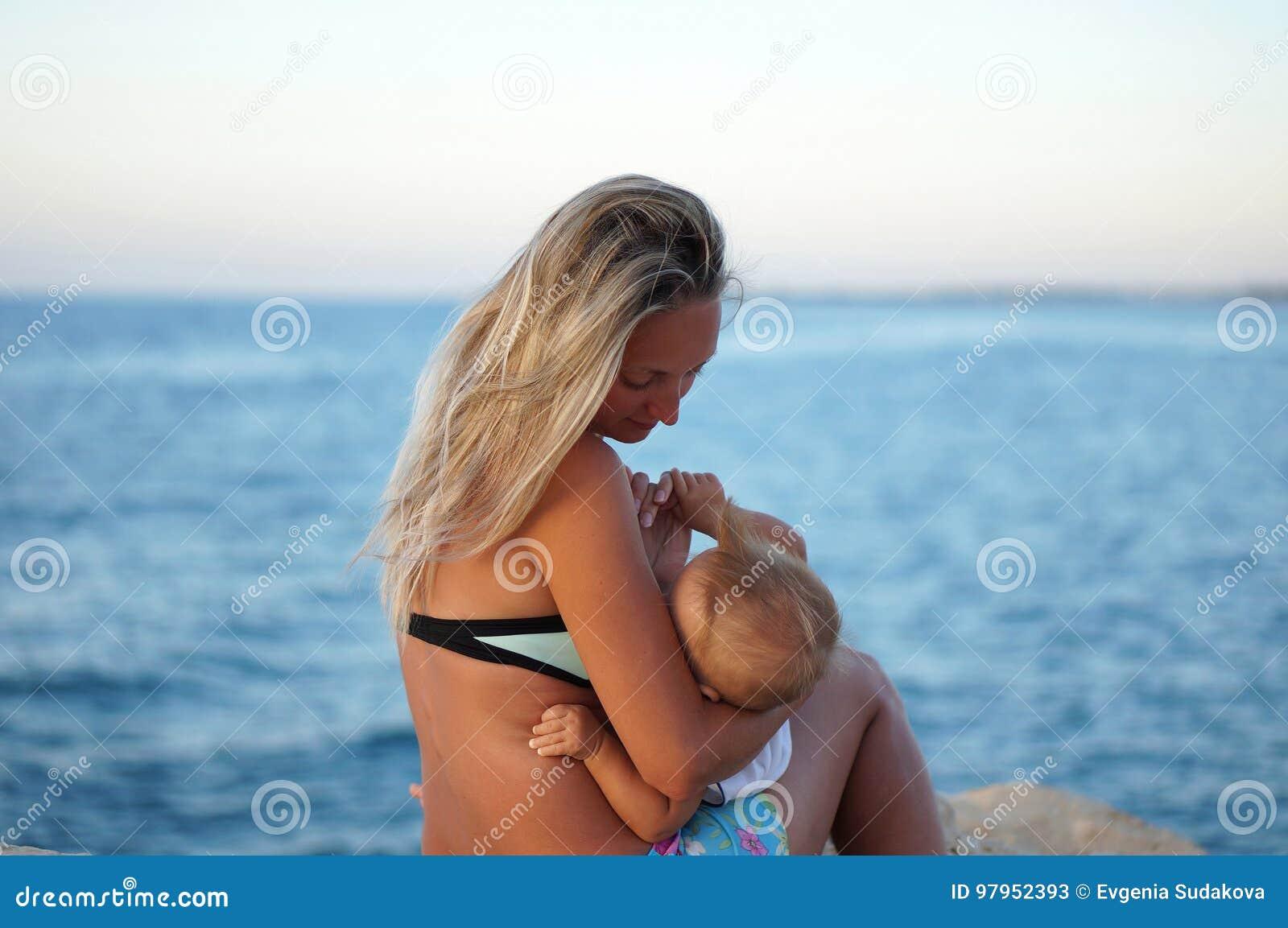 Macierzysty breastfeeding dziecko na plaży przy zmierzchem blisko morza Pozytywne ludzkie emocje, uczucia, radość Śmieszny śliczn