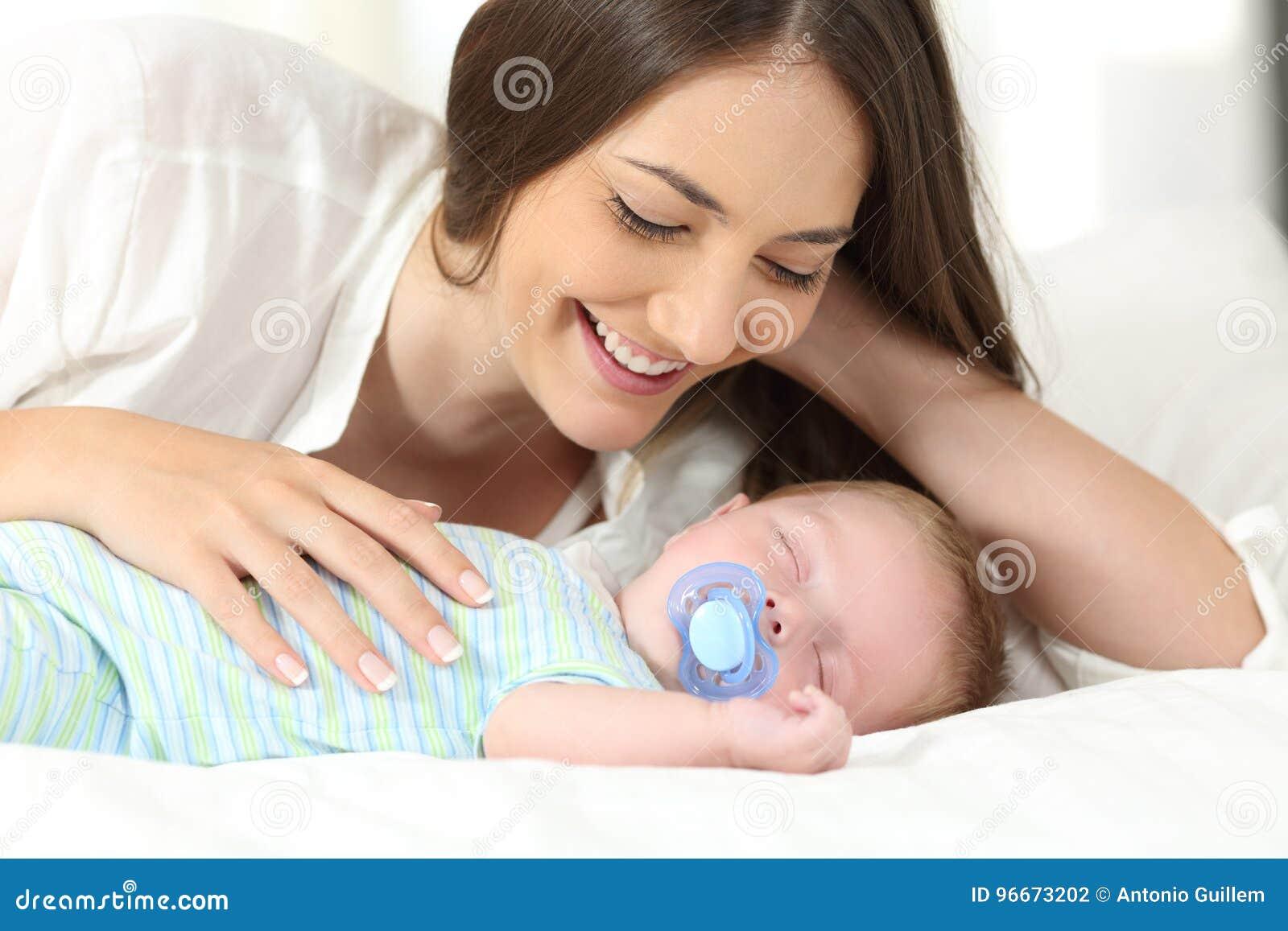 Macierzysty dopatrywanie jej dziecka dosypianie na łóżku