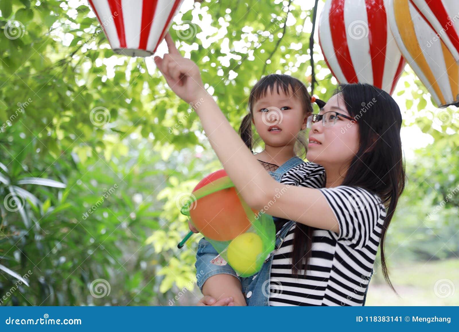 Macierzysty mama uścisk ściska jej córki uśmiechu śmiech zabawę cieszyć się czas wolnego w lato parka dziecka dzieciństwa szczęśl