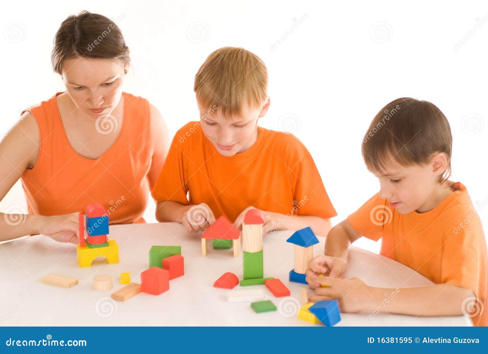 Macierzysty obsiadanie przy stołem z dwa synami
