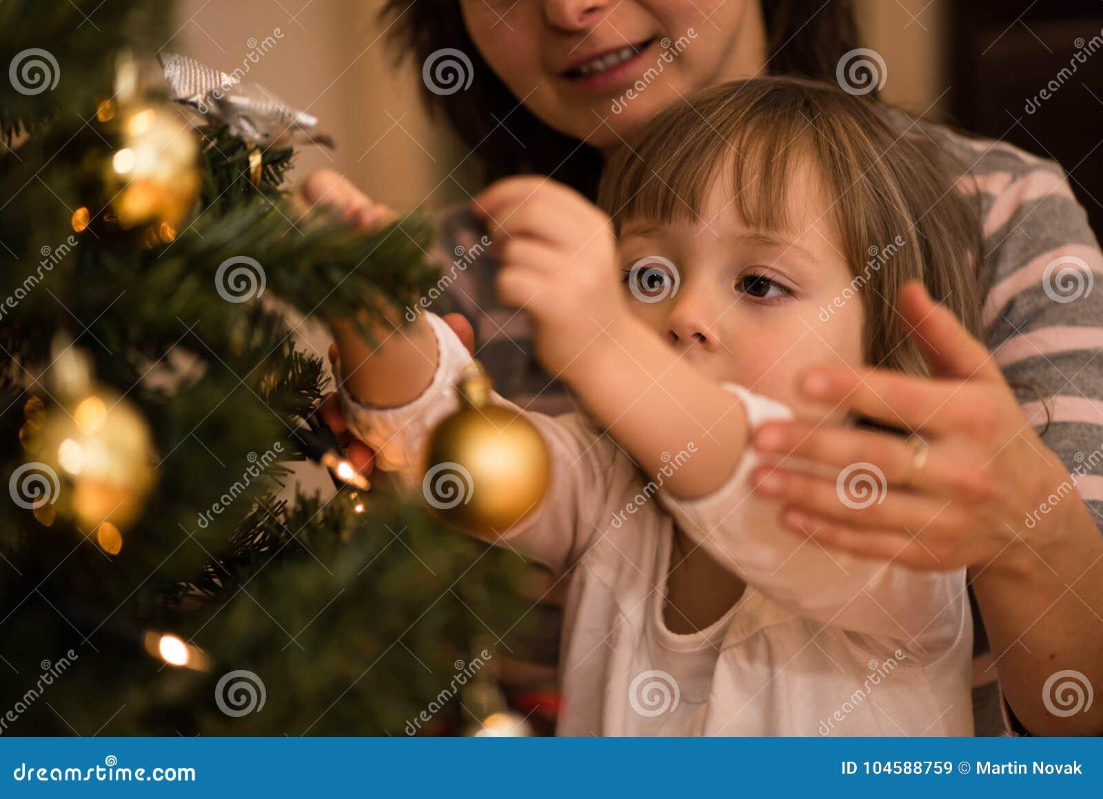 Macierzysty pomagać jej córki dekoruje xmas drzewa
