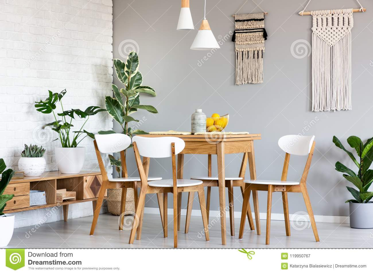 Macrame hanging on gray wall above wooden table and chairs in br