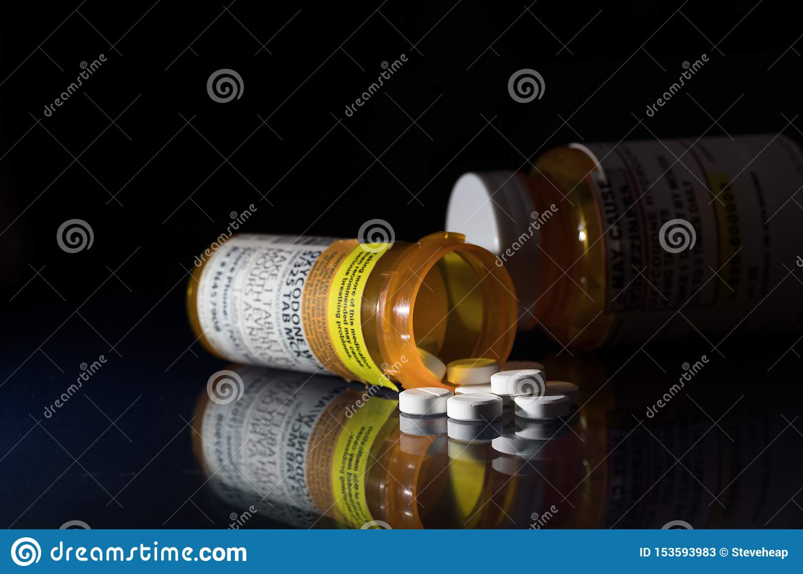 Macro de tabuletas do opiáceo do oxycodone com as garrafas da prescrição contra o fundo escuro