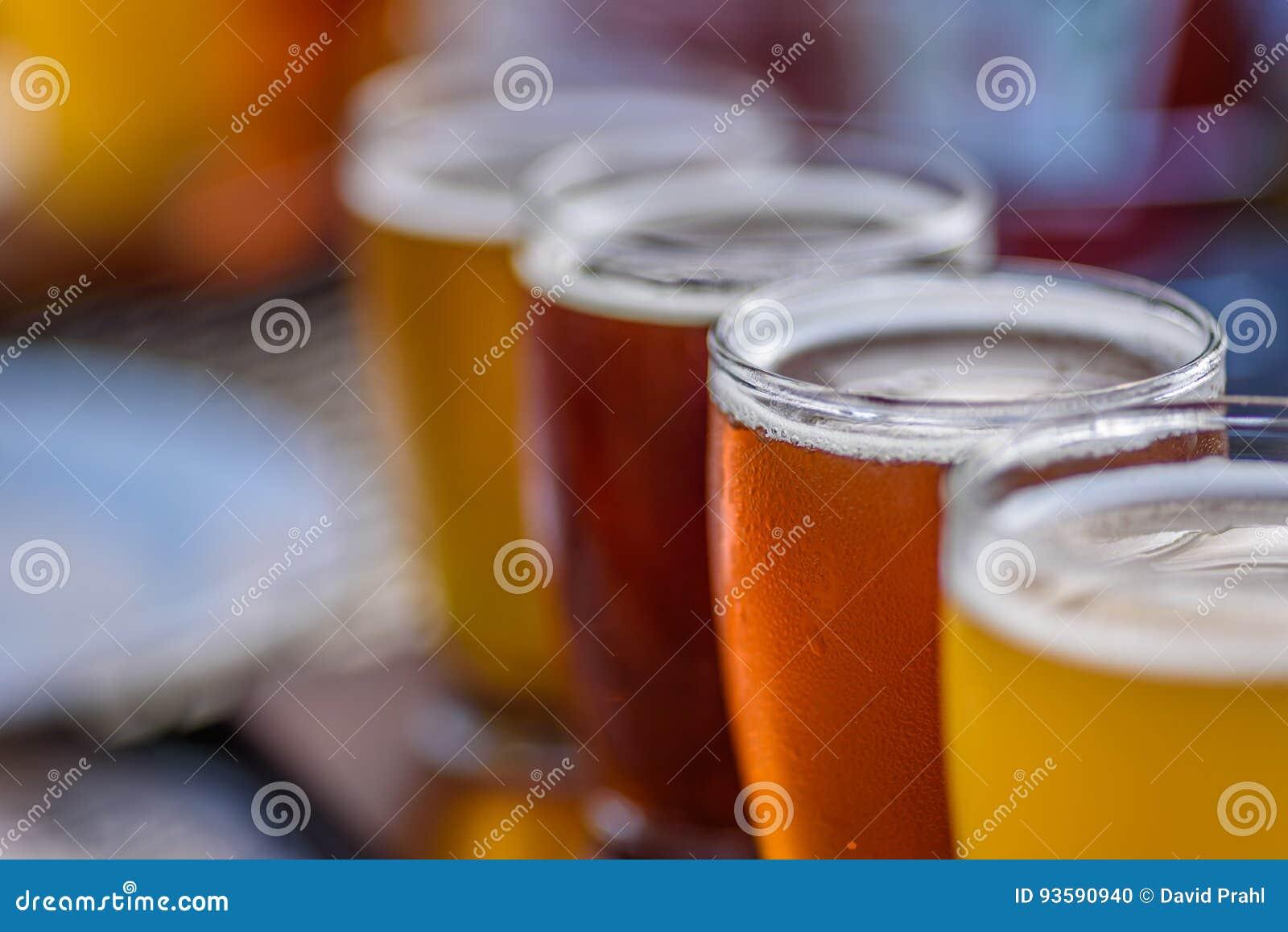 Macro del primer de un vuelo de la cerveza en luz del sol