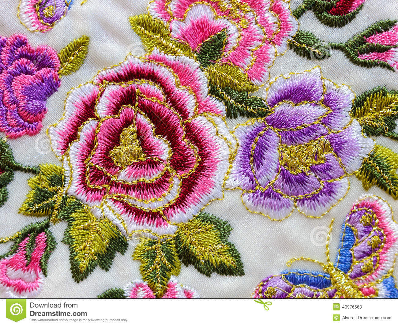 Beautiful embroidery with vivid flowers on white textile background