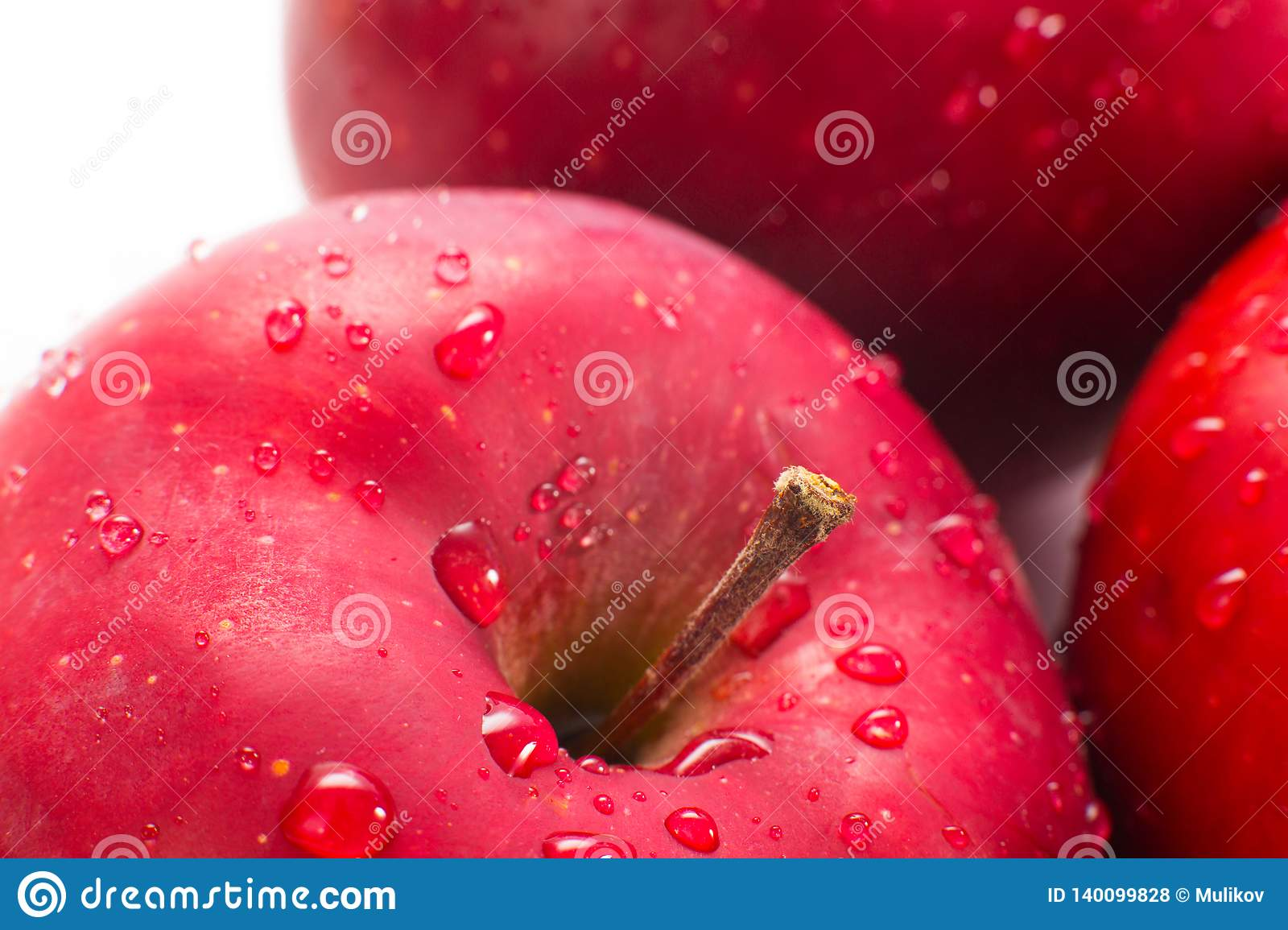 Macro of fresh red wet apples with drops.