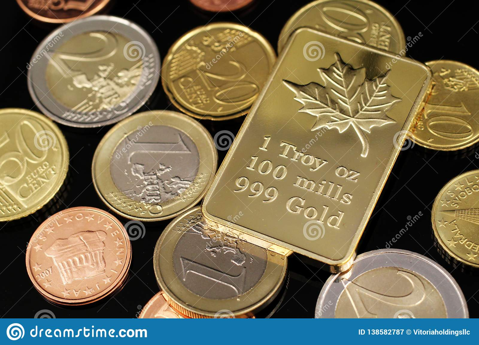 A close up image of Euro coins with a Canadian gold ingot on a black background