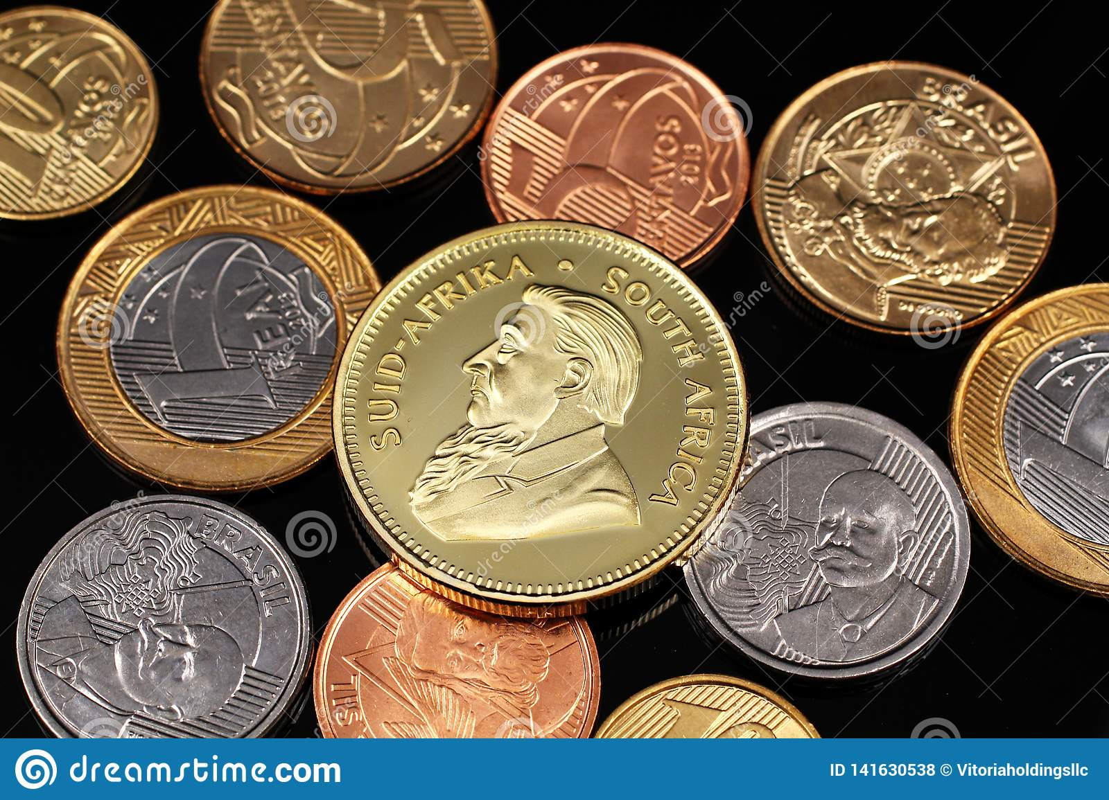 An assortment of Brazilian coins on a black reflective background with a South African one ounce gold Krugerrand coin