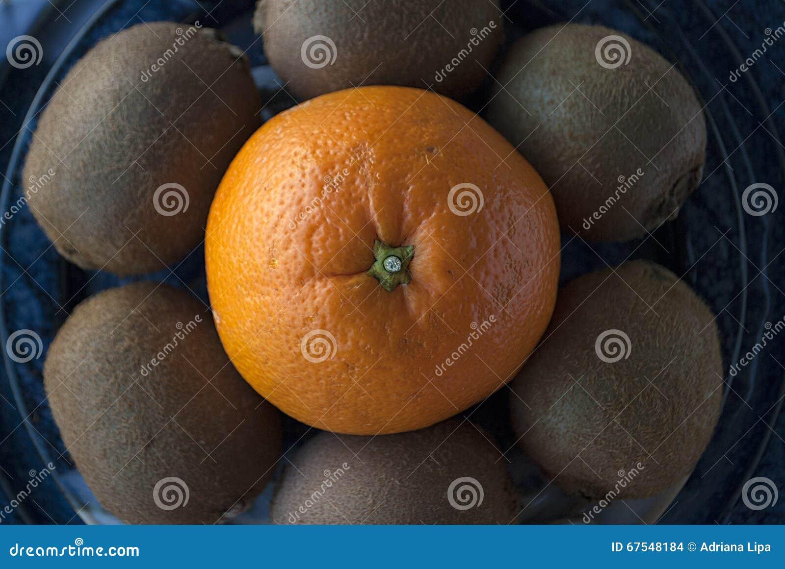 Macro shot of an orange surrounded by kiwis