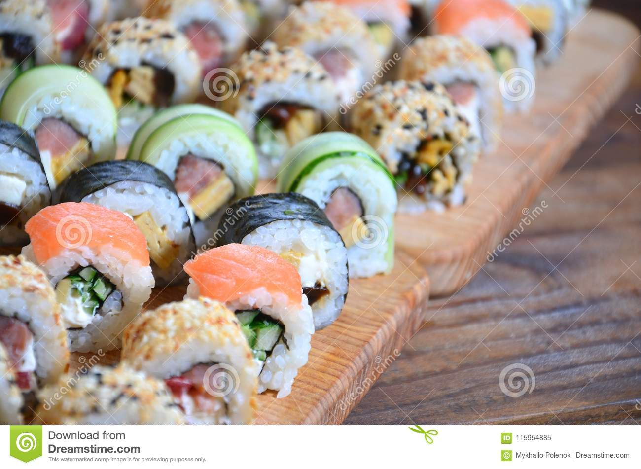 A macro shot of a sushi set of many rolls is located on a wooden cutting board on a table in the kitchen of a sushi bar. A tradit