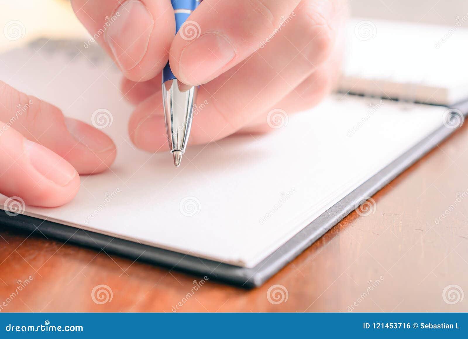 Macro van een Mannelijke Hand die in een Lege Organisator With een Biro schrijven