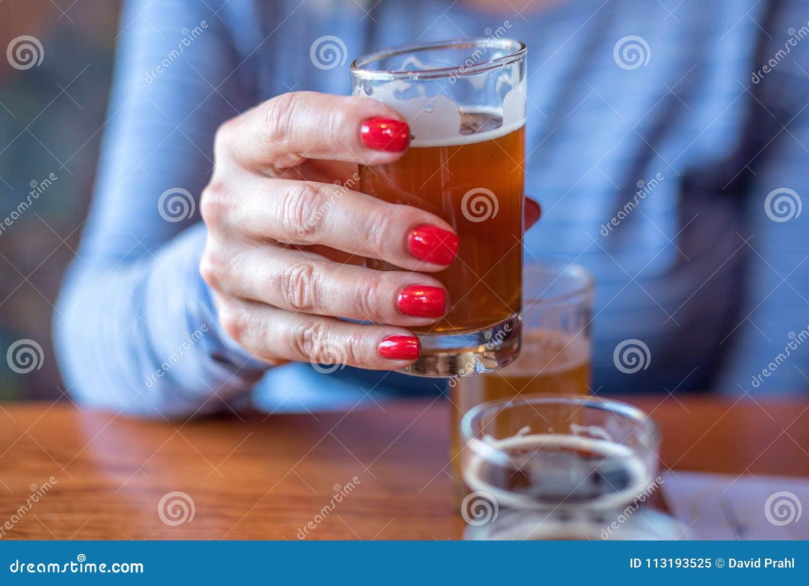 Macroclose-up van vrouw die een glas van biervlucht houden