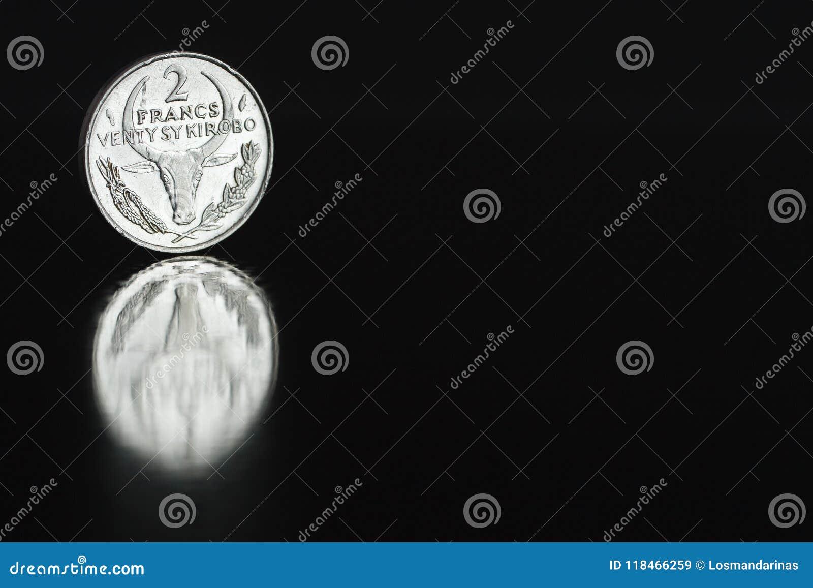 Madagassisk franc 1981 för mynt två på kanten på svart bakgrund med reflexion