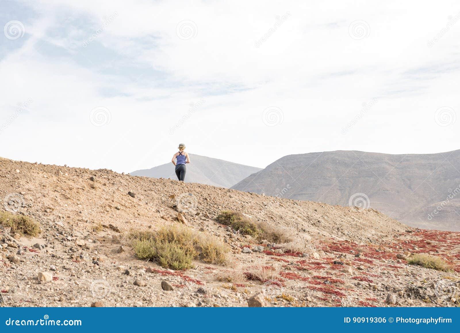 Madame active Running sur la voie chaude de désert pour la forme physique