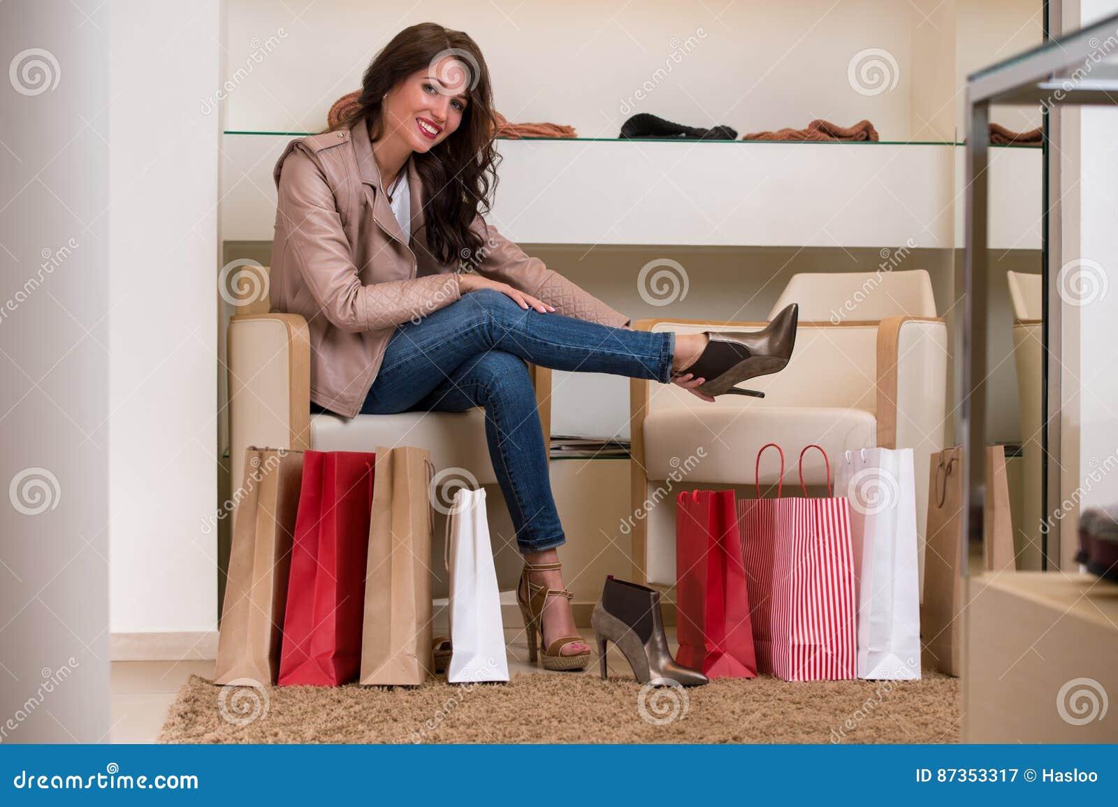 Madame essayant sur plusieurs paires de nouvelles chaussures dans le magasin