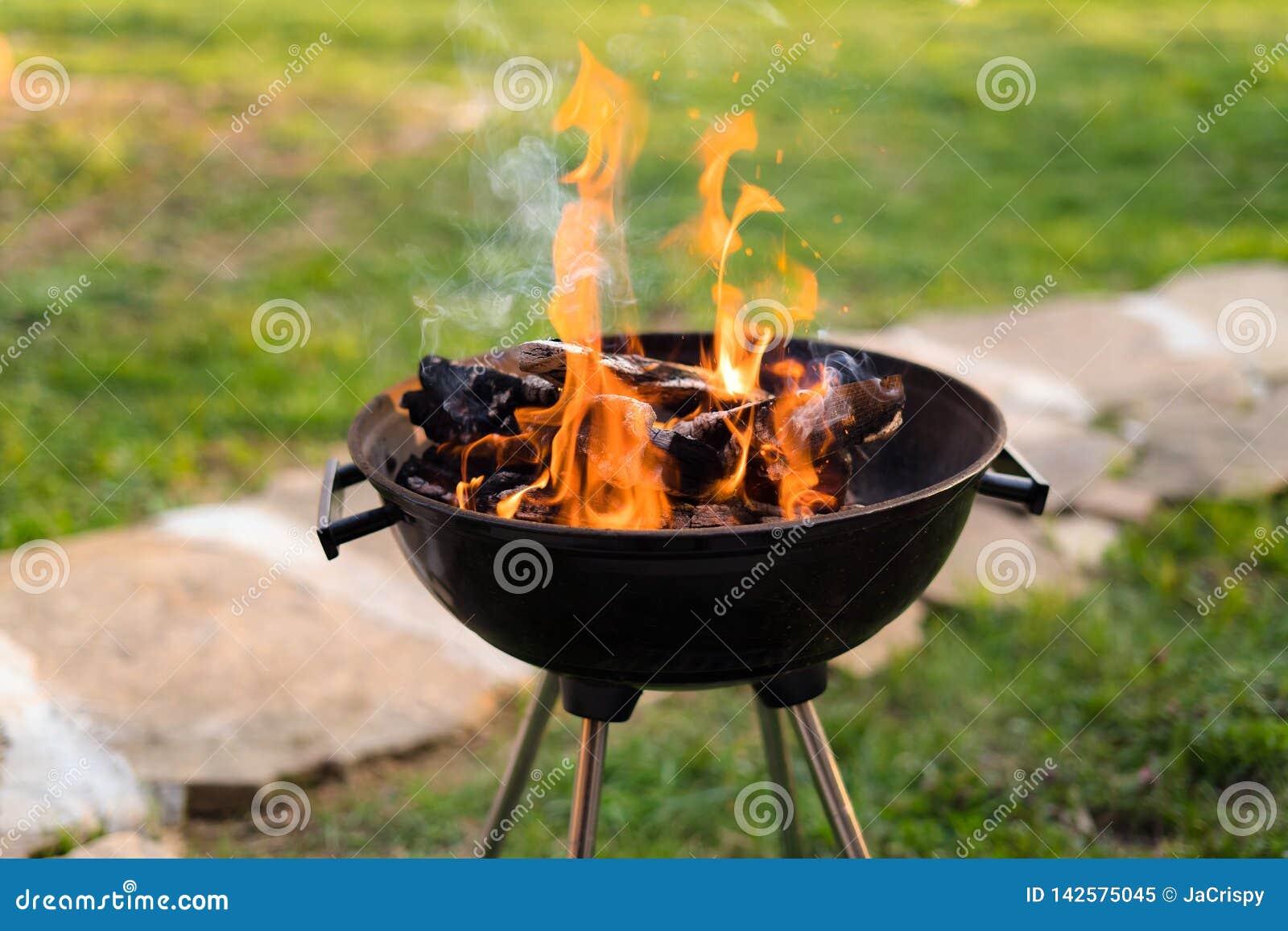 Madeira de queimadura na grade do assado, preparando carvões quentes para grelhar a carne no pátio traseiro Profundidade de campo