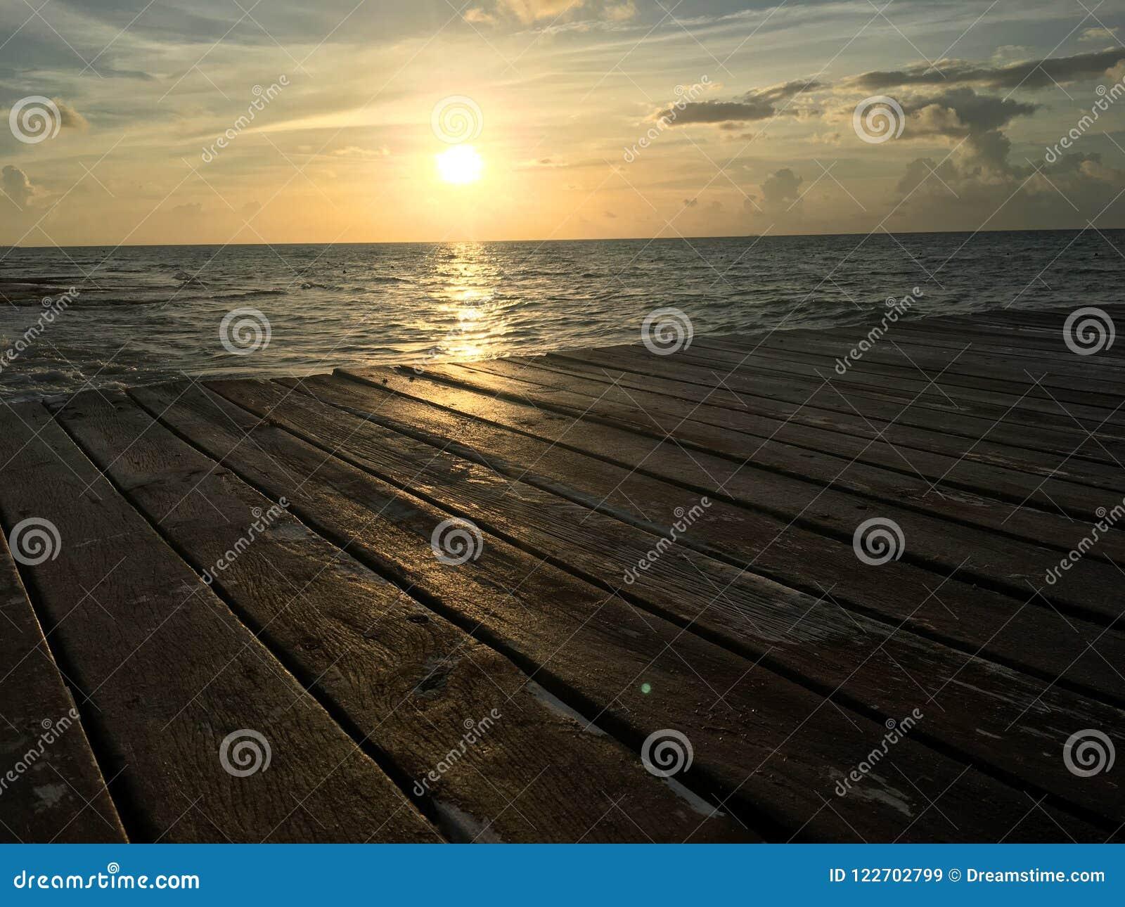 Madera del muelle de la agua de mar de la salida del sol