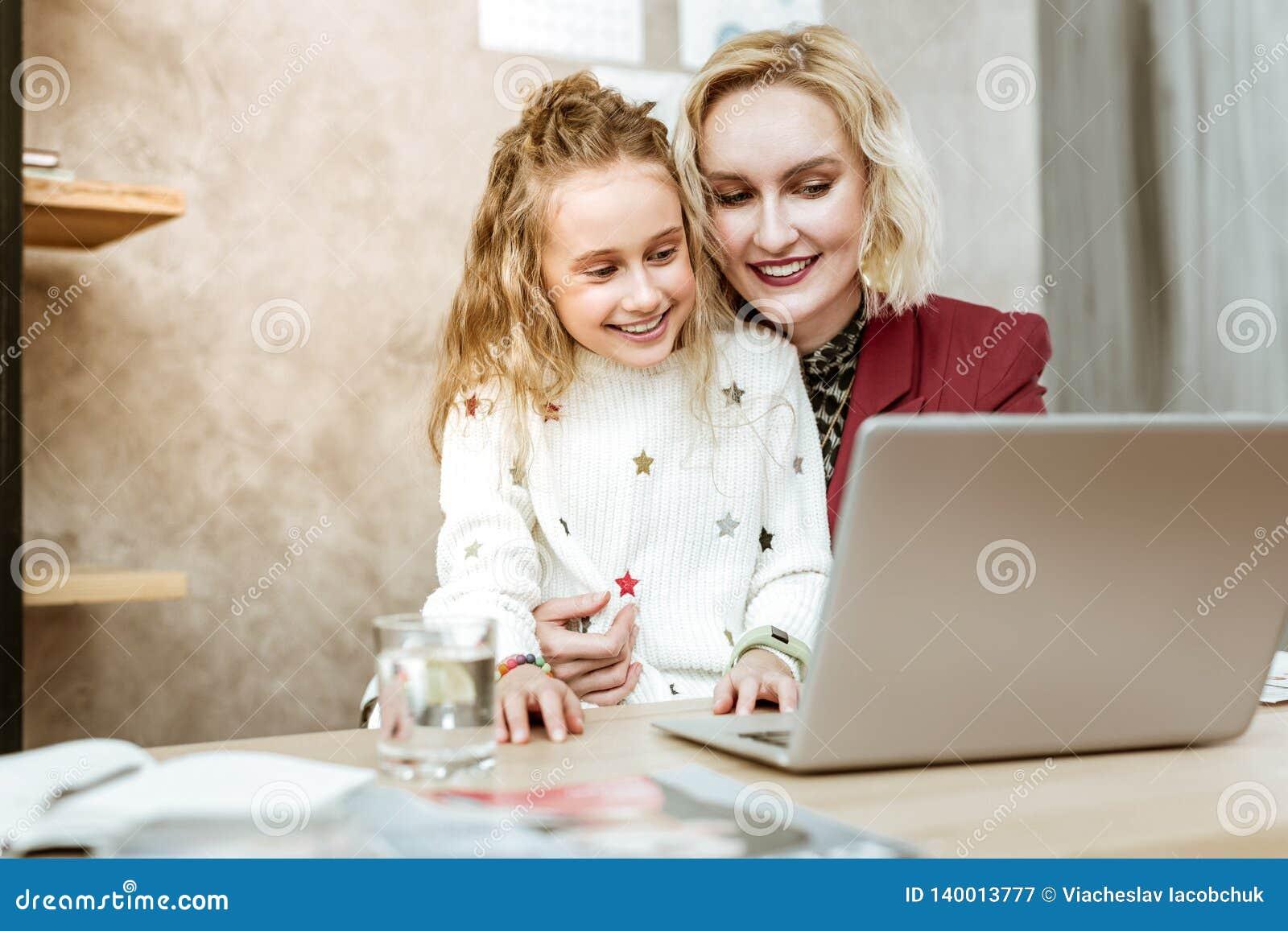 Madre adulta apuesta con la sonrisa amplia que lleva a su hija