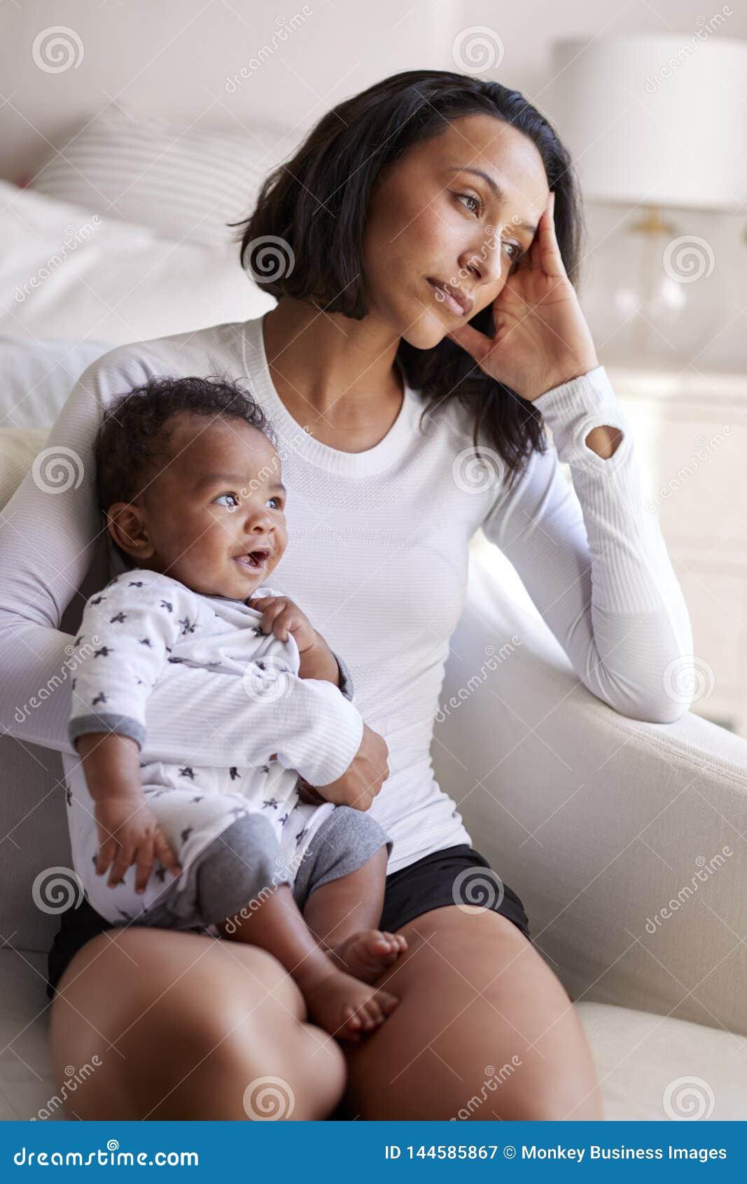 Madre adulta joven que se sienta en una butaca en su dormitorio, deteniendo a su viejo hijo de tres meses del bebé, mirando lejos