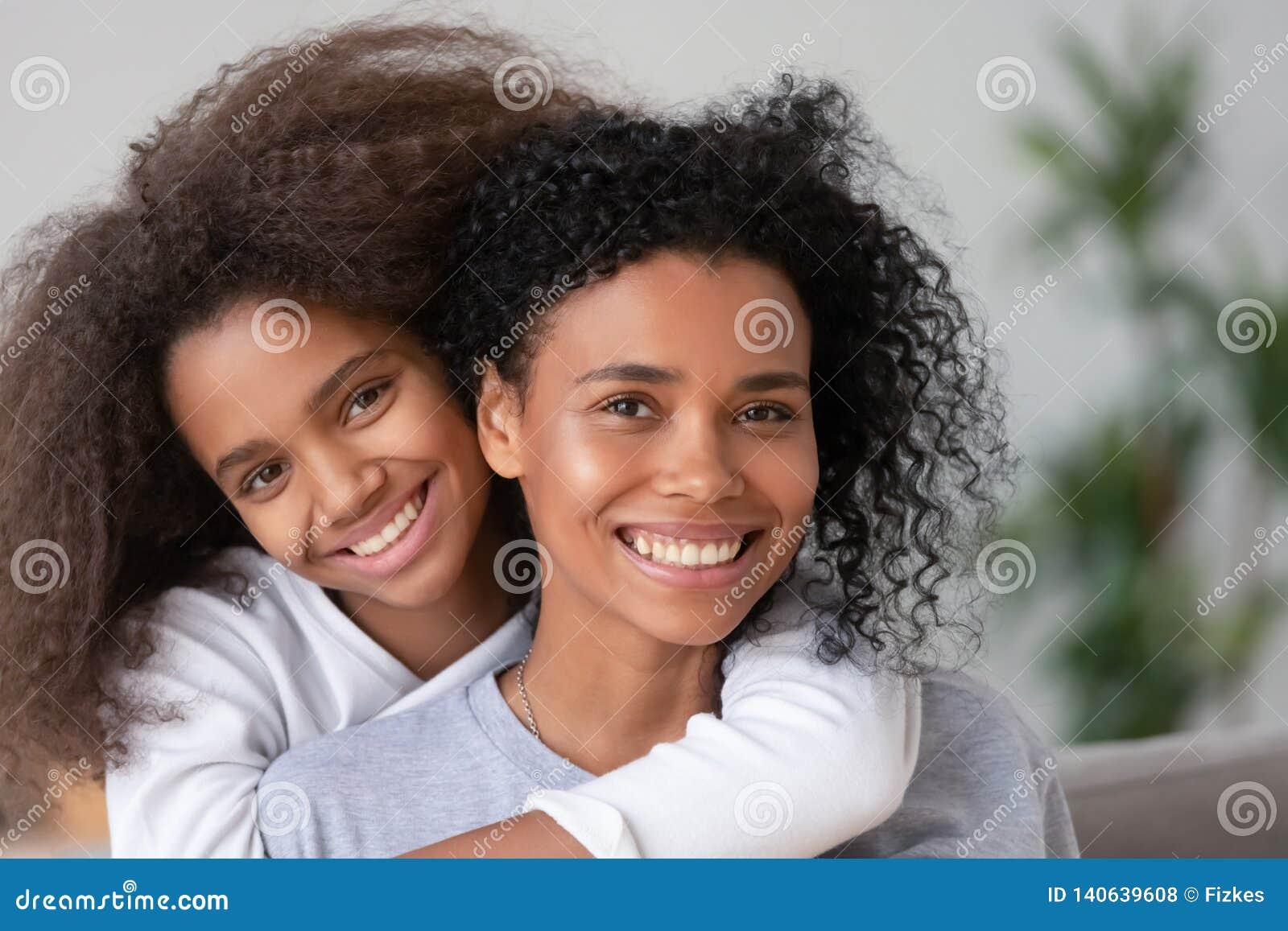 Madre africana e hija felices que abrazan mirando la cámara