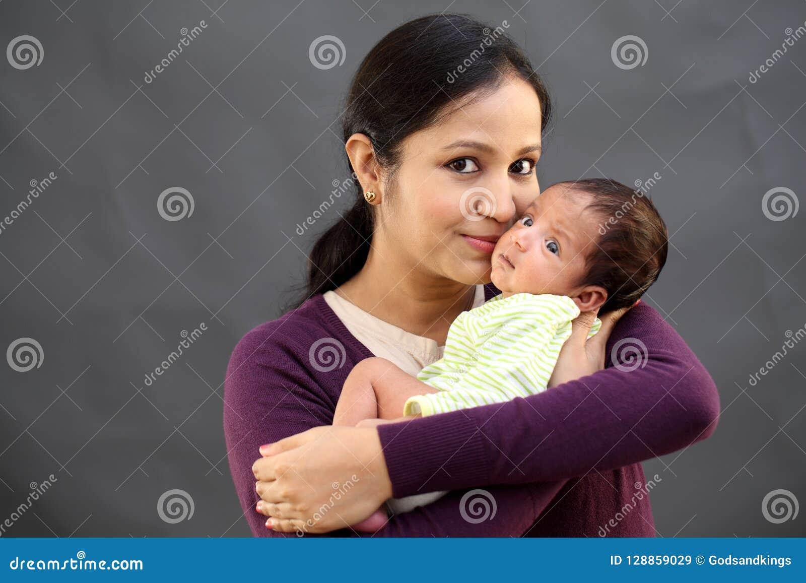 Madre alegre que juega con recién nacido