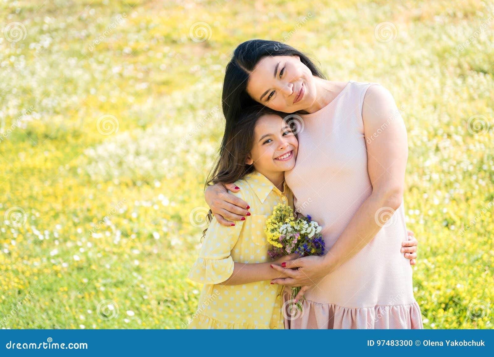 Madre allegra e figlia che abbracciano sul prato