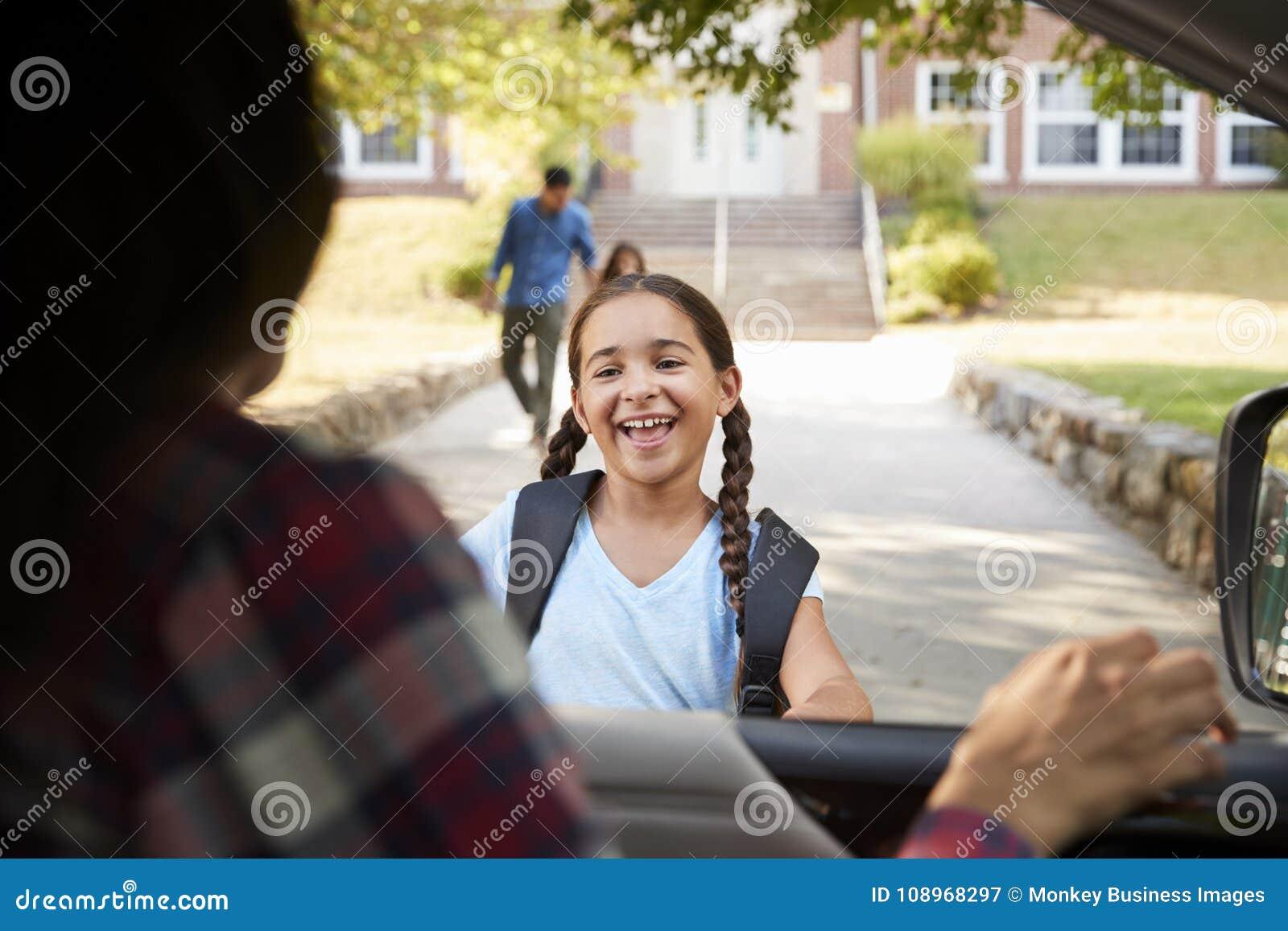 Madre in automobile che raccoglie figlia in Front Of School Gates