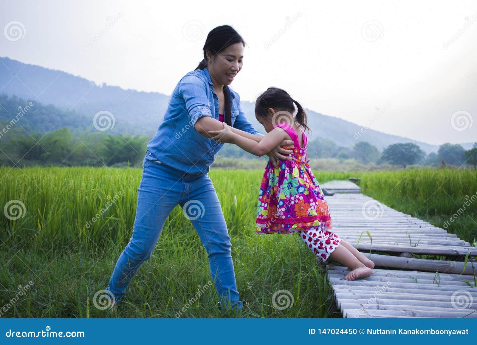 Madre ayudar a su ni?o a cruzar la corriente, hija de elevaci?n de la madre en campo del arroz