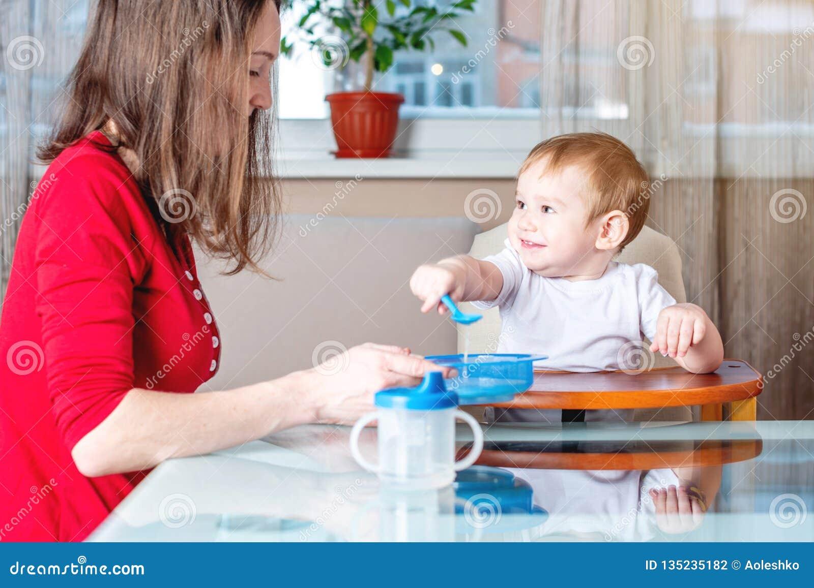 Madre che alimenta la mano della tenuta del bambino con un cucchiaio di alimento Nutrizione sana del bambino Le emozioni di un ba