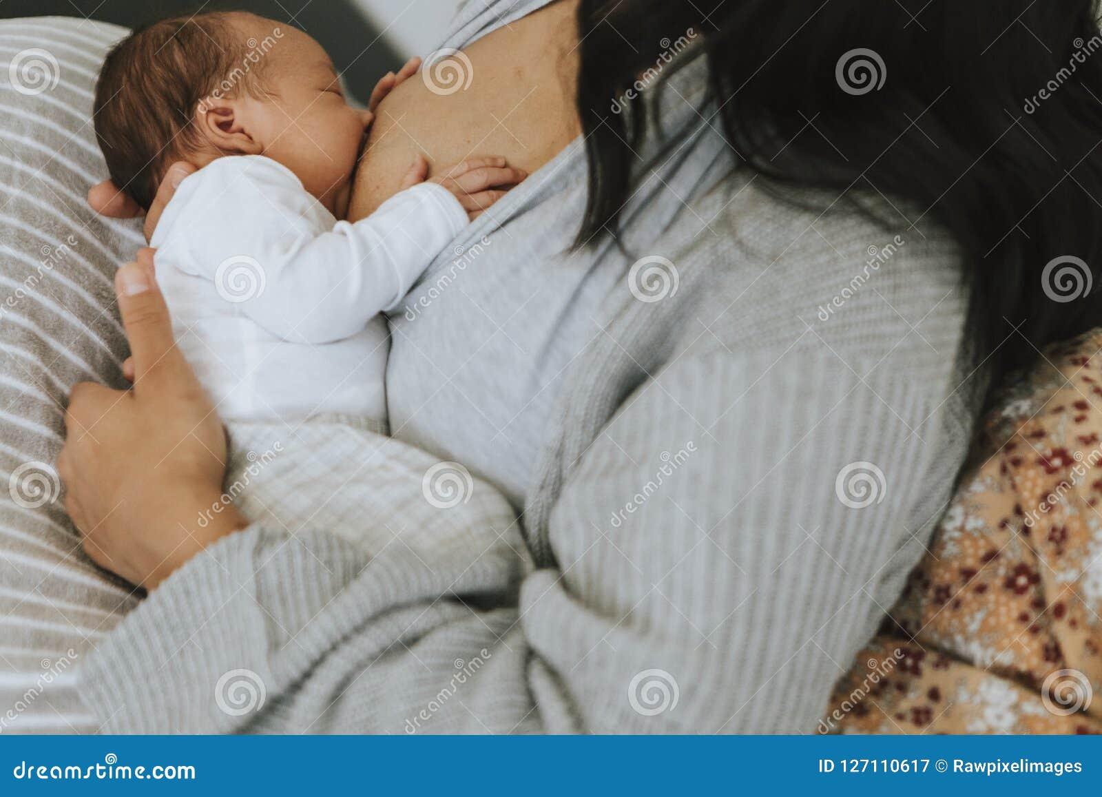 Madre che allatta al seno il suo bambino sul letto