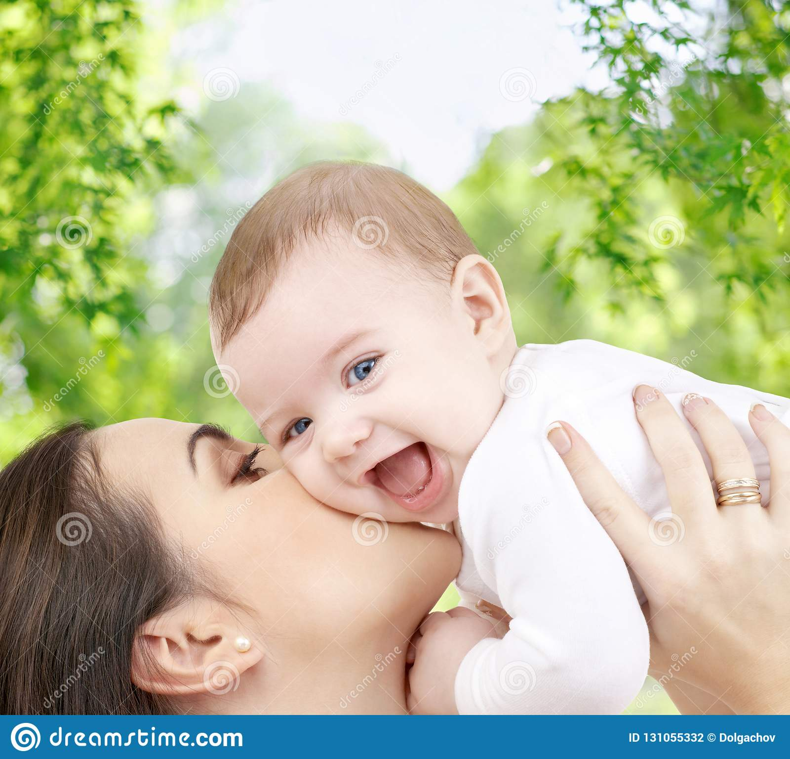 Madre che bacia bambino sopra sfondo naturale verde