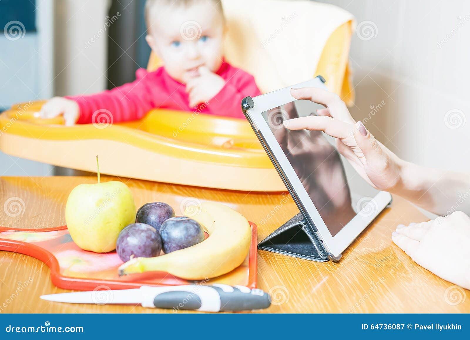 Madre che cerca ricetta della preparazione di alimenti per bambini