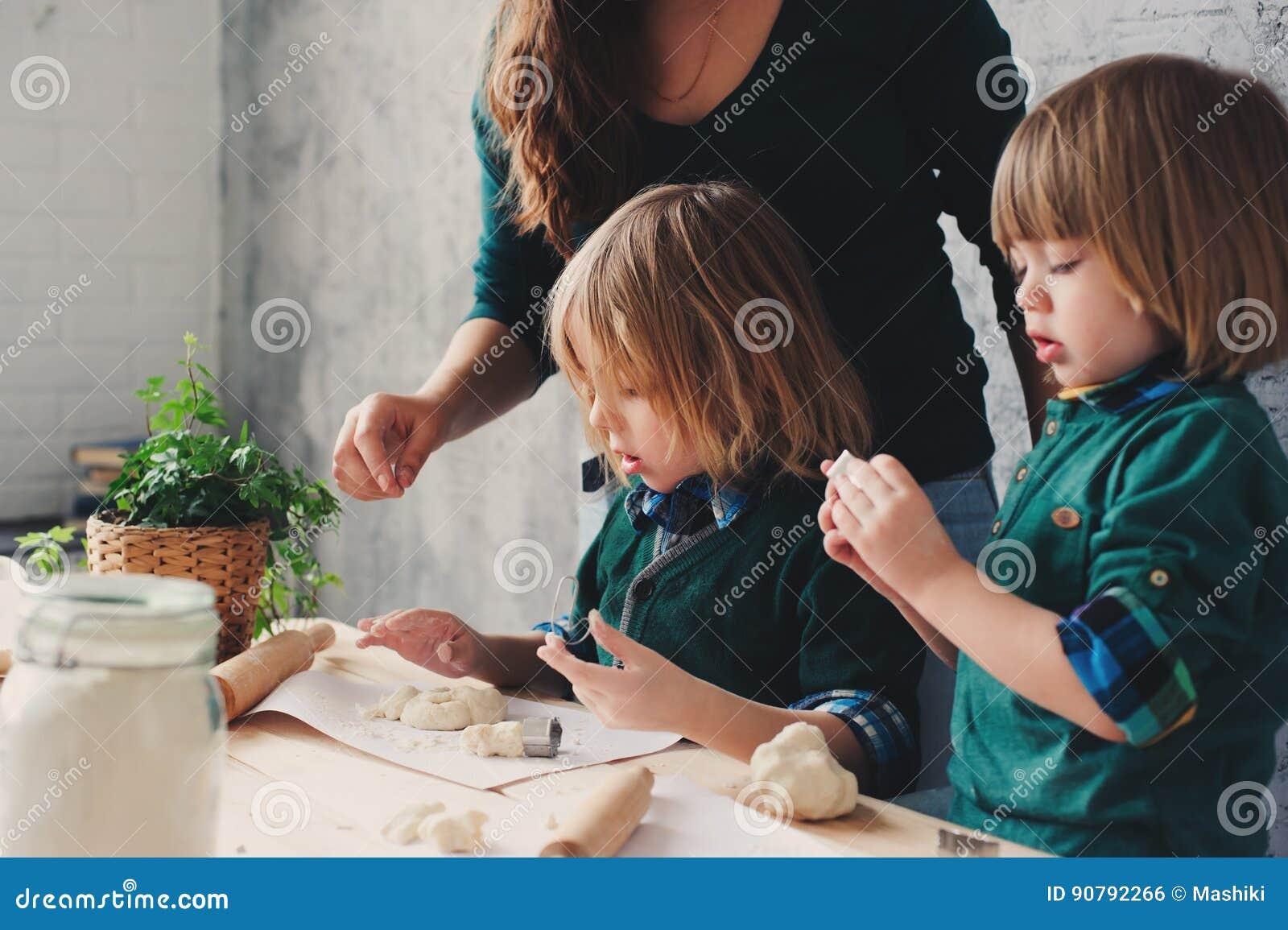 Madre che cucina con i bambini in cucina Fratelli germani del bambino che cuociono insieme e che giocano con la pasticceria a cas