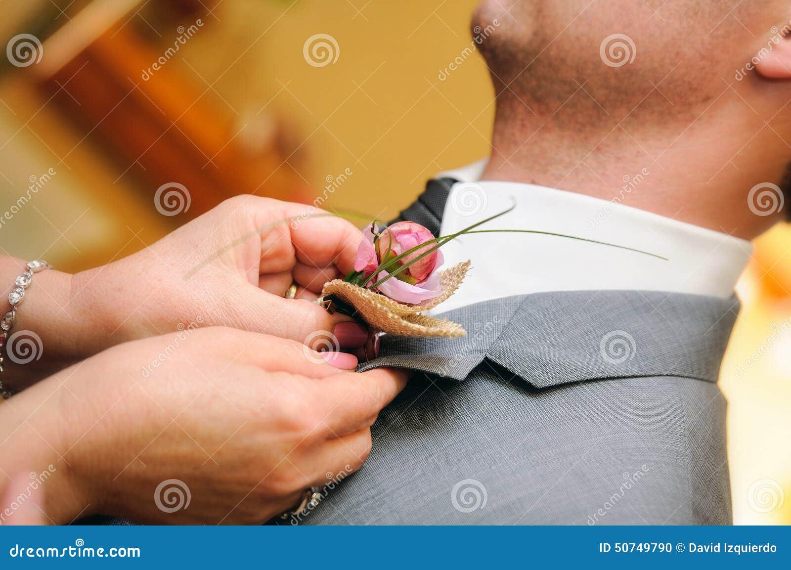 Madre che mette un fiore nell occhiello del vestito dallo sposo
