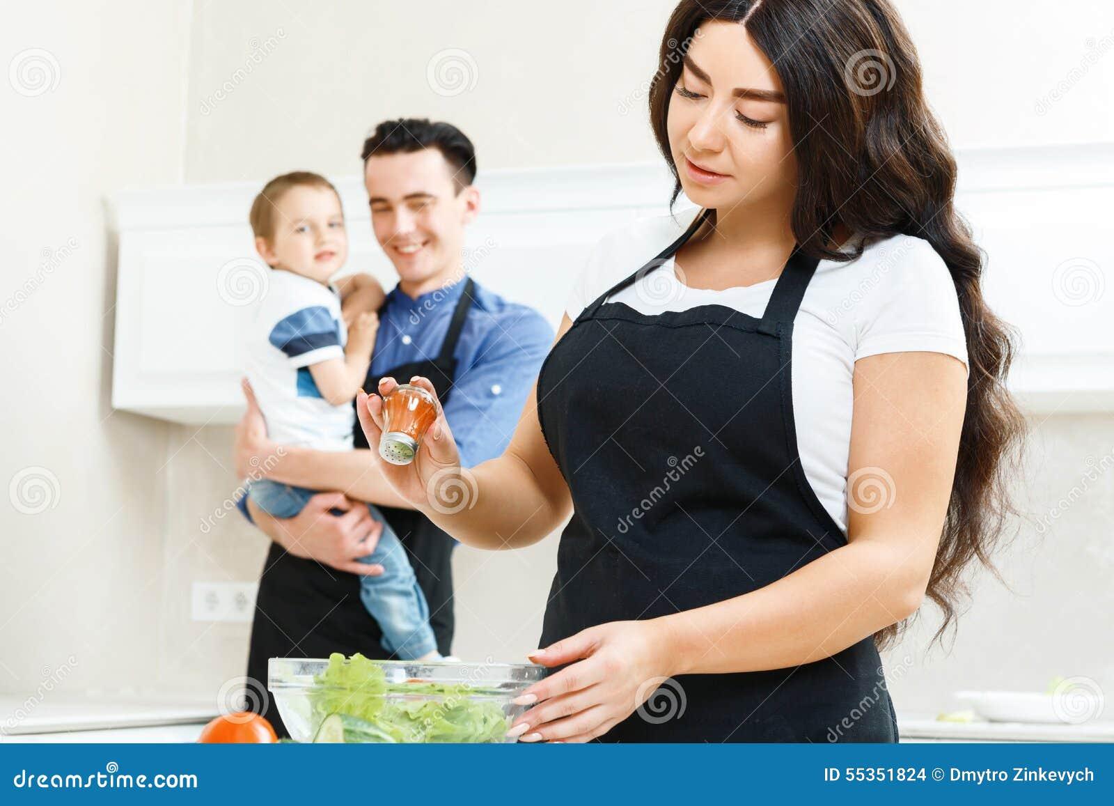 Madre che sala insalata in cucina