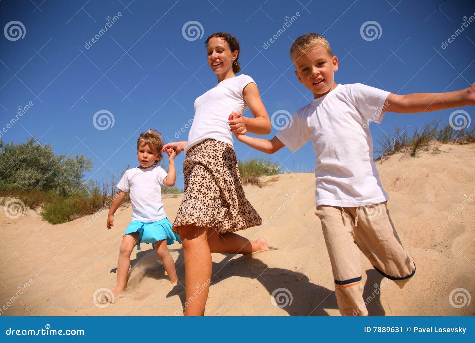 Madre con corridas de los niños en la arena